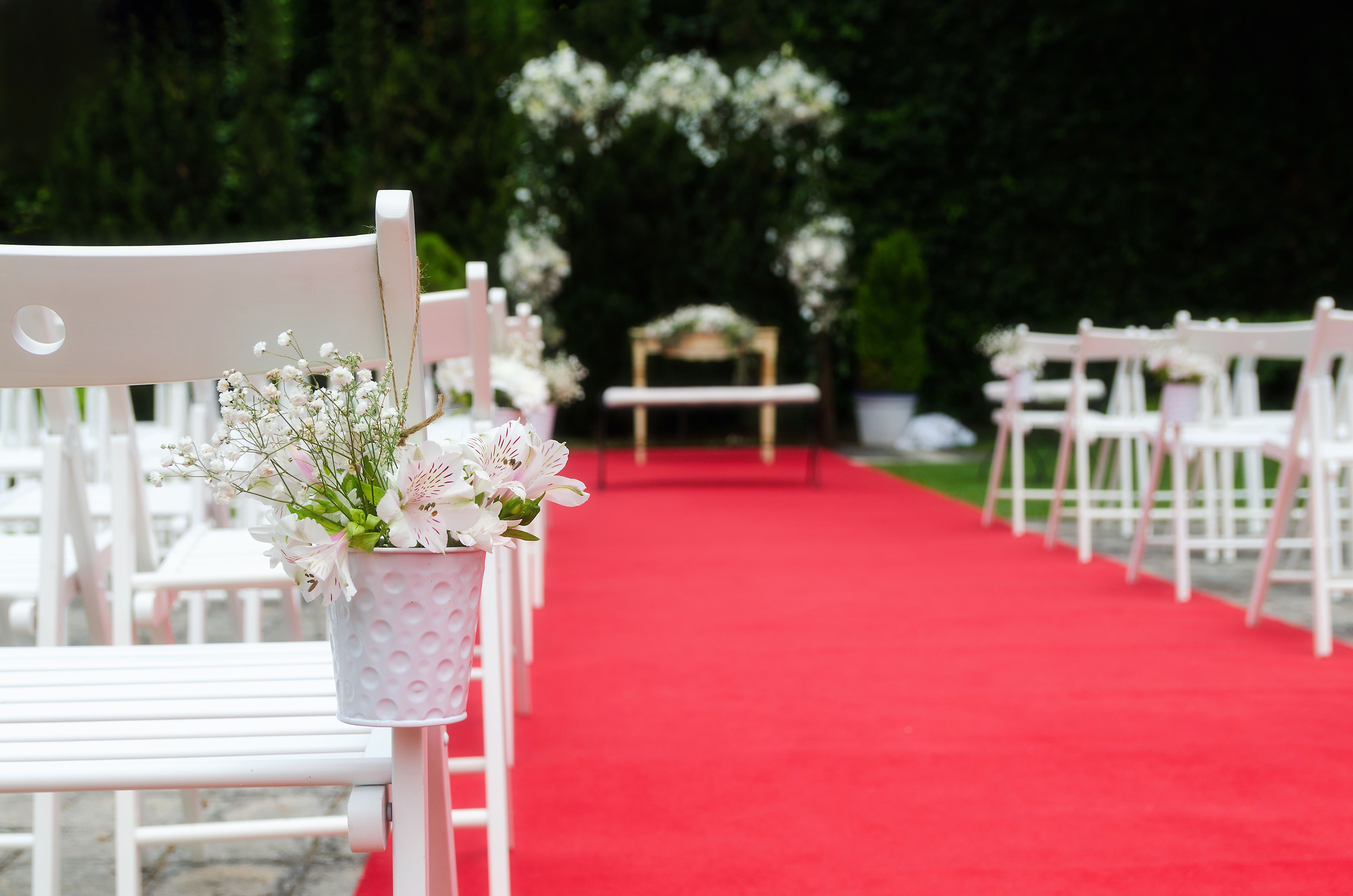Beautiful Wedding ceremony decoration, rustic altar decorated with lilies, alstroemerias and chrysanths flowers behind  ivy wall, red carpet with whites chairs. Wedding day concept. Space for text.