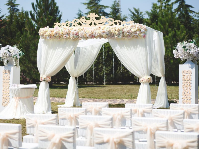 White wedding tent for the ceremony outdoors. Arch. Chairs.